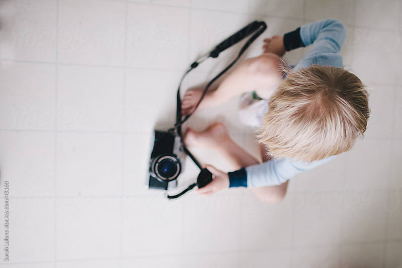 A little boy playing on the floor with a vintage camera. by Sarah Lalone for Stocksy United