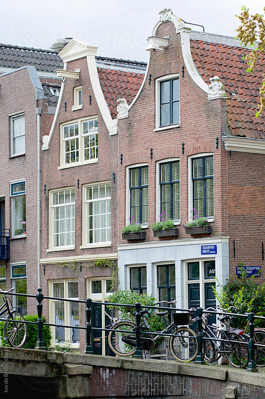 Two canal houses with classic facades in Amsterdam with a bridge and classic bikes in the foreground by Ivo de Bruijn for Stocksy United