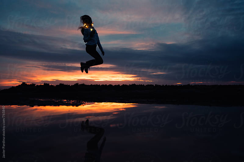 reflection of jumping girl with light at sunset by Javier Pardina for Stocksy United
