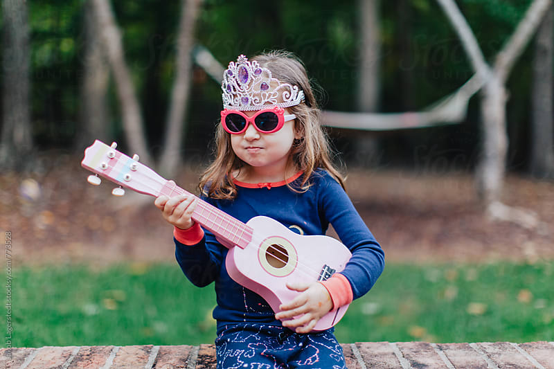 Funny young girl playing a toy guitar  by Jakob for Stocksy United