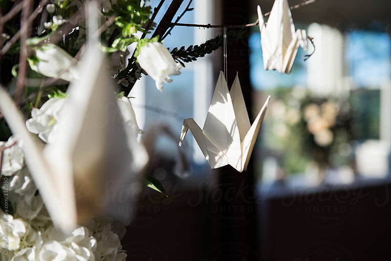 White origami paper cranes hang from twigs in a floral centerpiece by Cara Dolan for Stocksy United