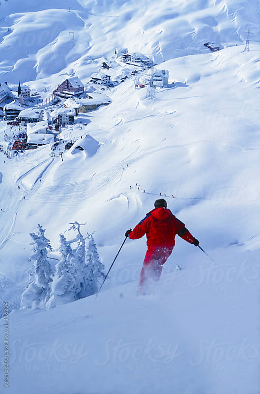 Man in red jacket skiing powder snow in winter mountains by Soren Egeberg for Stocksy United