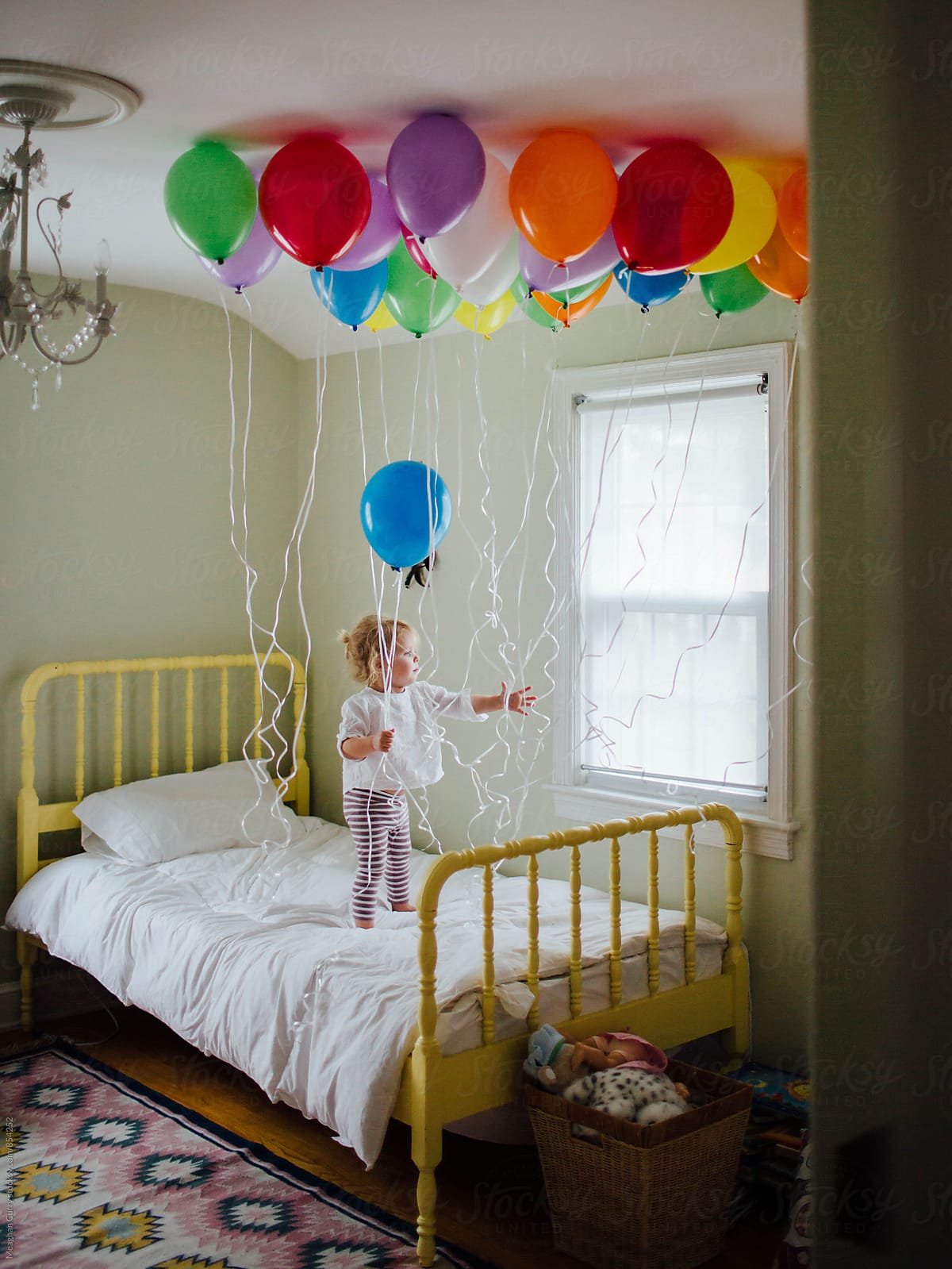 Little Girl On Her Bed Holding Birthday Balloons By Meaghan Curry For Stocksy United