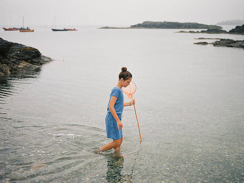 Girl looking for fish with a net by Léa Jones for Stocksy United