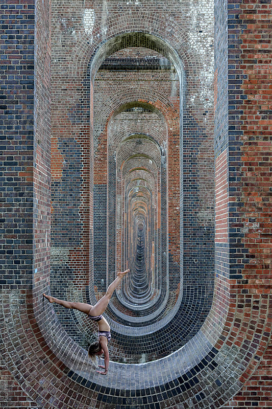 Female 20s. Yoga exersize inside arches of railway viaduct by Paul Phillips for Stocksy United