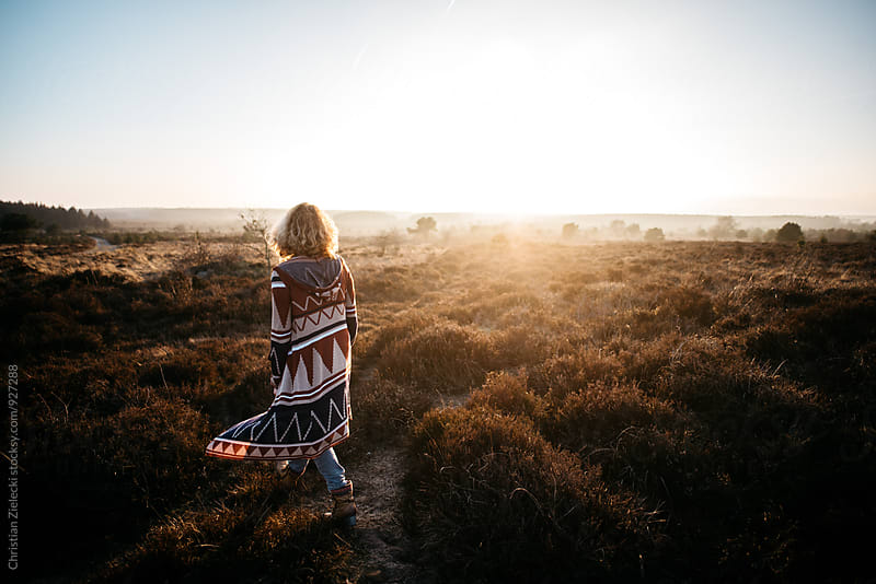 A woman walking in the heath in sunset light by Christian Zielecki for Stocksy United