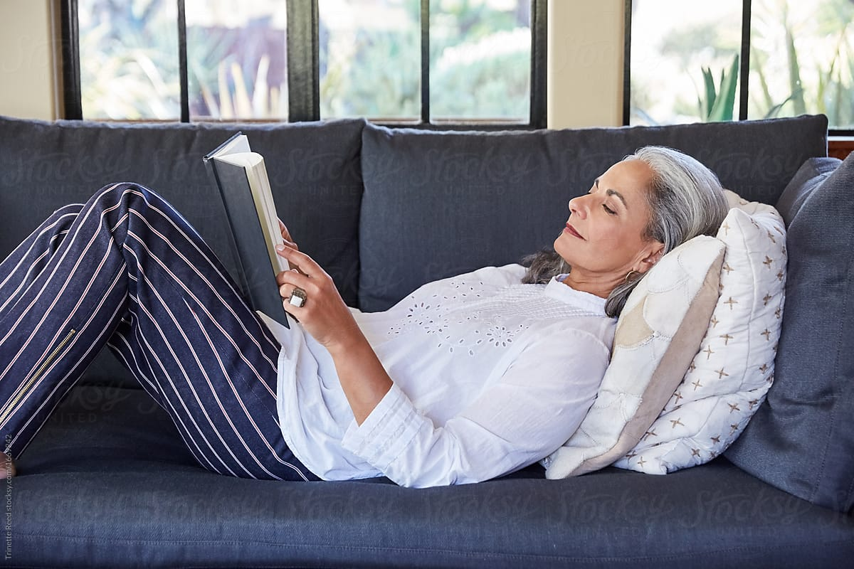 Mature woman with grey hair reading a book lying down on