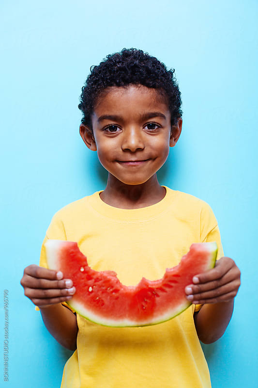 Little boy holding a bite watermelon on blue wall. by BONNINSTUDIO for Stocksy United