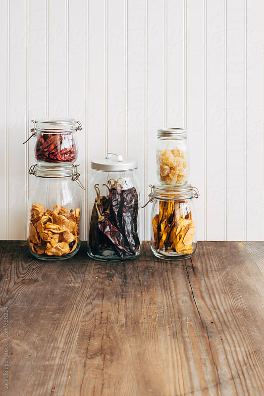 Glass jars with dried mango, peppers, ginger, and apples. by Lucas Saugen for Stocksy United