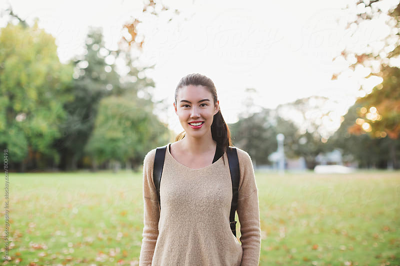 Young mixed race woman - asian & caucasian - looking at camera outside with backpack on fall day by Rob and Julia Campbell for Stocksy United