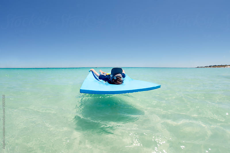 Boy relaxing on a large foam mat in the turquoise water of the Indian Ocean by Angela Lumsden for Stocksy United