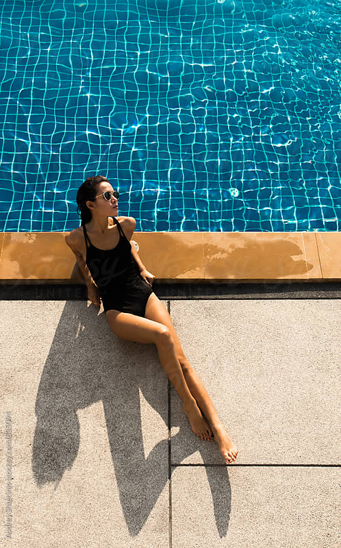 Beautiful young woman in black tricot sunbathing by the pool on hot summer day. by Audrey Shtecinjo for Stocksy United