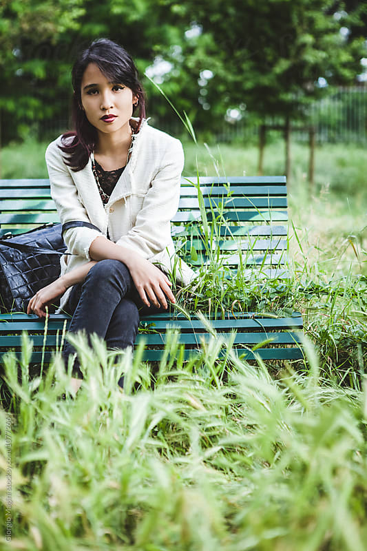 Asian Teenage Girl Bored on a Bench by Giorgio Magini for Stocksy United
