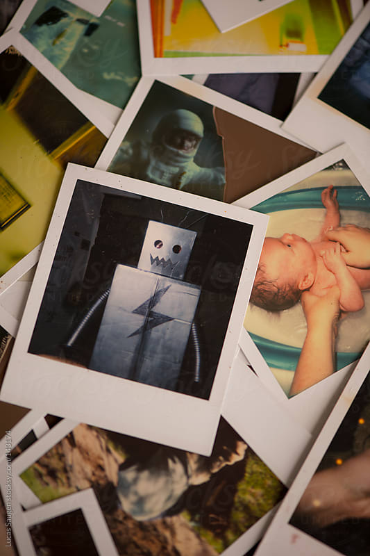 Instant photos in a pile including one of a robot costume and one of a newborn baby getting a bath. by Lucas Saugen for Stocksy United