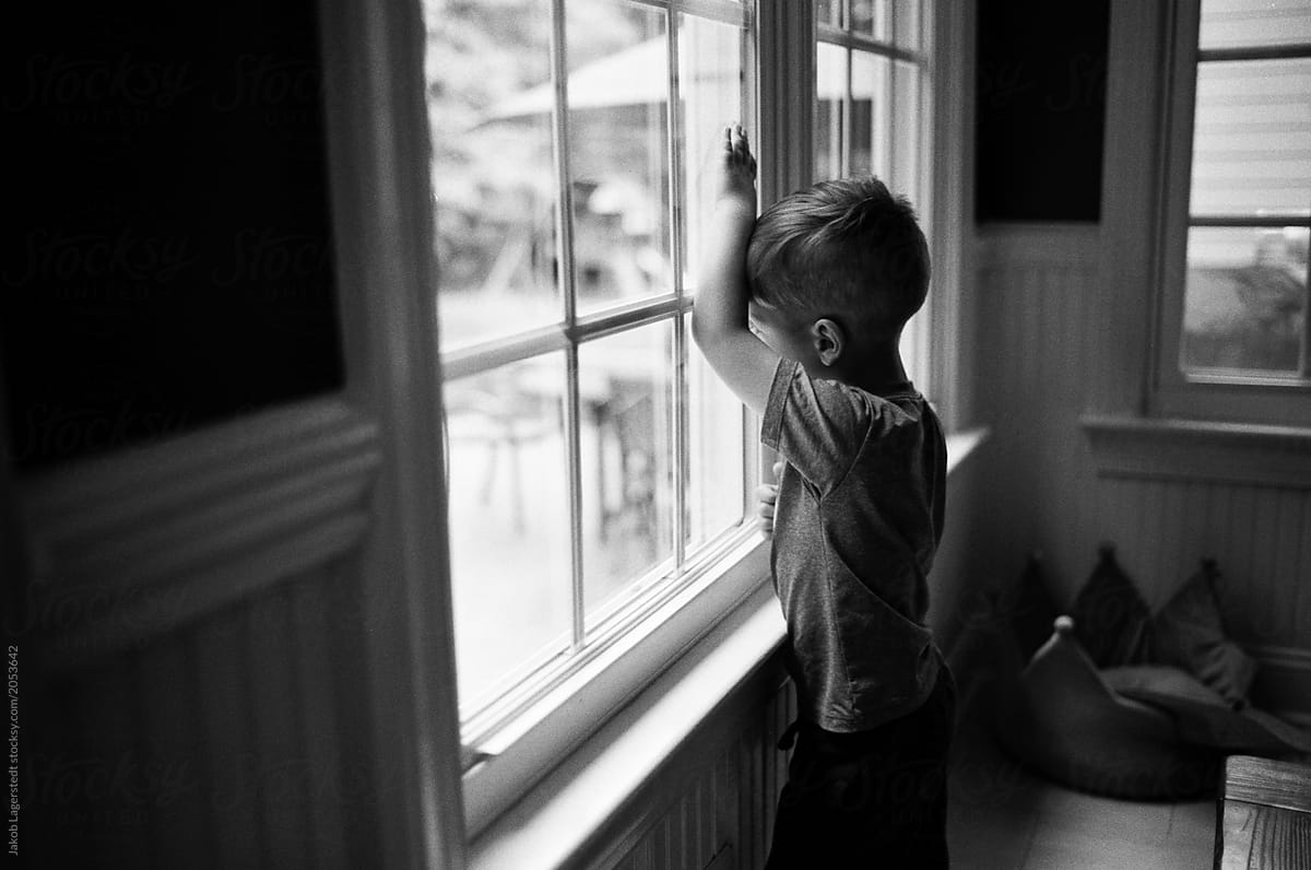 Moody Black And White Images Of A Bored Young Boy Looking Out A Window By Jakob Lagerstedt Young Boy Bored Stocksy United