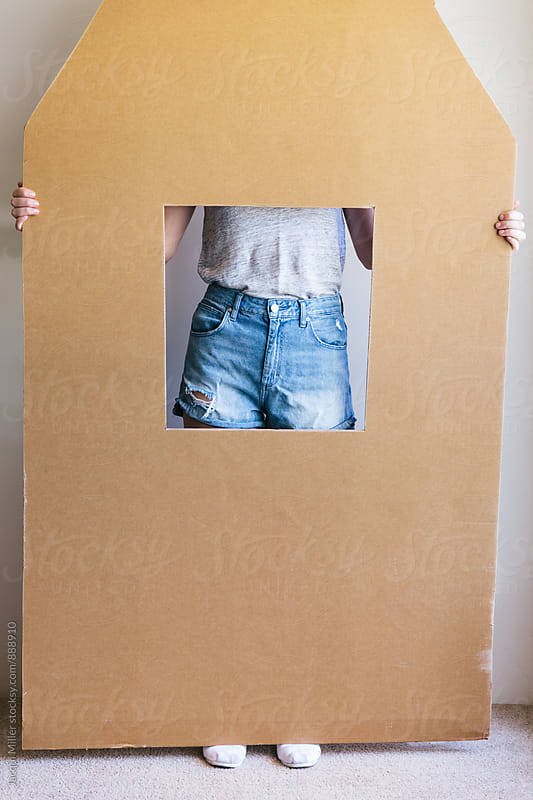 Unrecognisable female standing behind a large piece of cardboard with a window in the middle by Jacqui Miller for Stocksy United