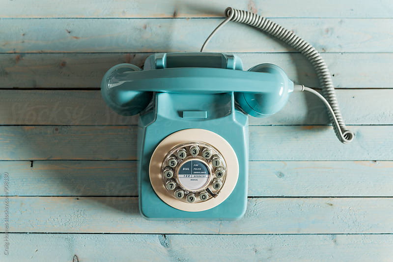 A blue retro telephone on a blue background by Craig Holmes for Stocksy United