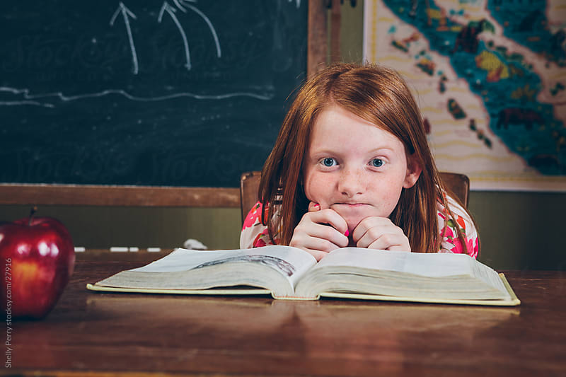 School girl at her desk with an open book. by Shelly Perry for Stocksy United
