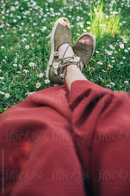 Female feet in daisies by Maja Topcagic for Stocksy United