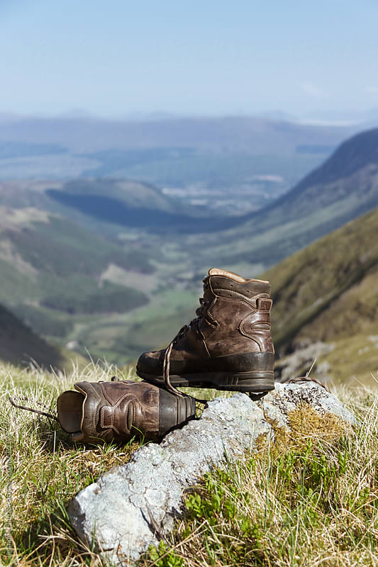 mountaineering boot with scottish highlands in the back by Leander Nardin for Stocksy United