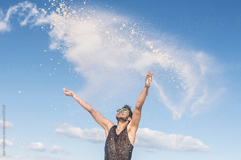 throwing sand in the wind ,handsome young man playing on a sunny beach  by Igor Madjinca for Stocksy United