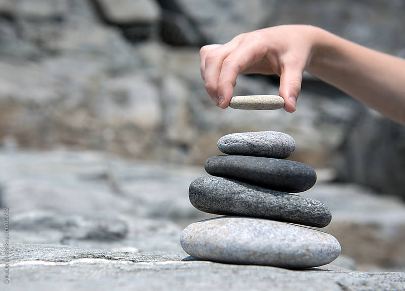 A child's hand places a rock on the top of a stack of smooth stones by Cara Dolan for Stocksy United