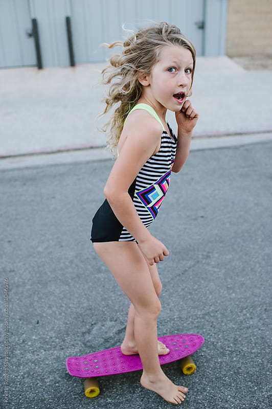 Cute blonde girl in swim suit skateboarding to beach by Kristin Rogers Photography for Stocksy United