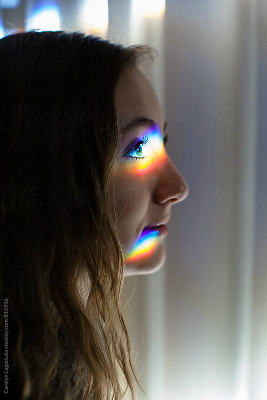 Teenage girl looking forward with a rainbow glowing prism on her face by Carolyn Lagattuta for Stocksy United