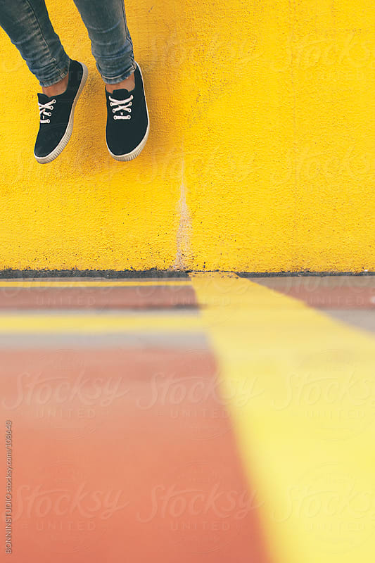 Young girl jumping in front of yellow wall.  by BONNINSTUDIO for Stocksy United