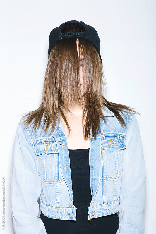 Young woman in cap and denim jacket with hair on face by Danil Nevsky for Stocksy United