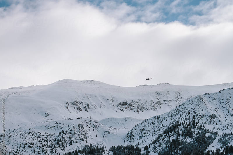 helicopter flying above snowcovered mountain landscape in kosovo by Leander Nardin for Stocksy United