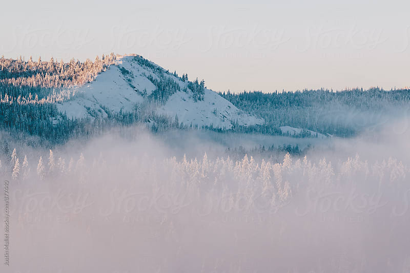 Fog lifting off the mountains on a cold winter morning by Justin Mullet for Stocksy United