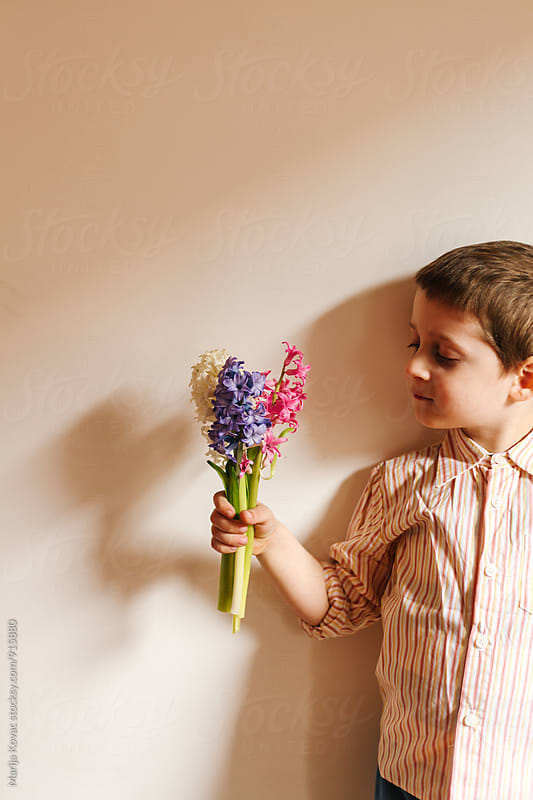 Boy holding flowers  by Marija Kovac for Stocksy United