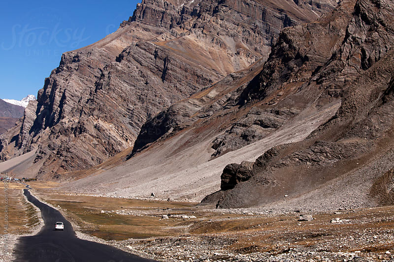 A car is moving through a asphalt  road and barren mountain in high altitude of Ladakh by PARTHA PAL for Stocksy United