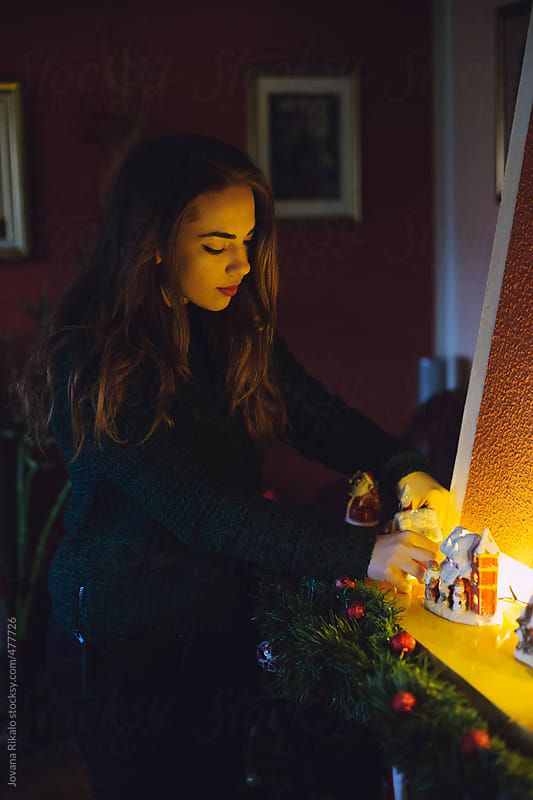 Young woman decorating a house for Christmas by Jovana Rikalo for Stocksy United