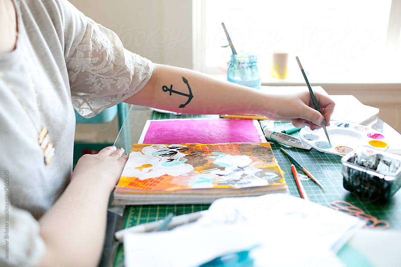 Artist creating colorful art on messy table  by Jennifer Brister for Stocksy United