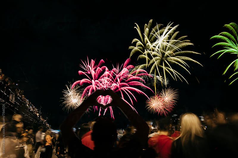 Man hands' silhouette shaping a heart in front of fireworks by Beatrix Boros for Stocksy United