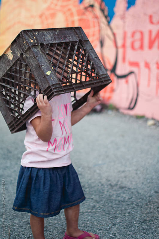 little girl wears milk crate on her head by Margaret Vincent for Stocksy United