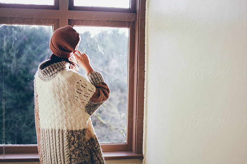Woman standing by a window by Treasures & Travels for Stocksy United