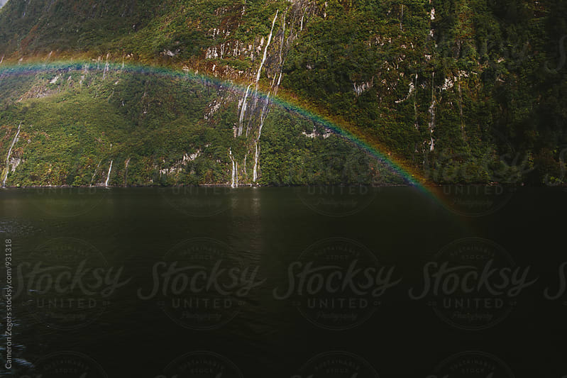 rainbow over water in fjord by Cameron Zegers for Stocksy United