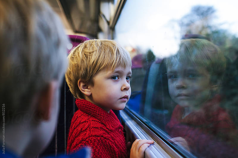 Little girl looking out of a train window. by Julia Forsman for Stocksy United