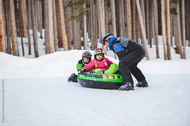 Father and two children playing with a toboggan in winter by Angela Lumsden for Stocksy United