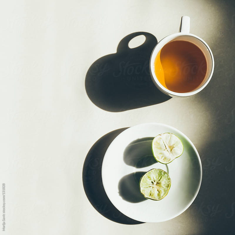 Cup of green tea and lemon on white surface. by Marija Savic for Stocksy United
