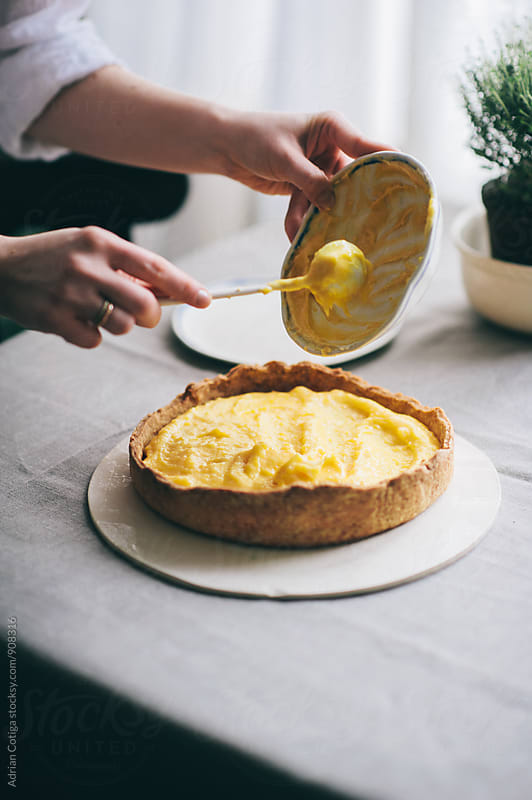 Pouring lemon filling on a  homemade tart with thyme by Adrian Cotiga for Stocksy United