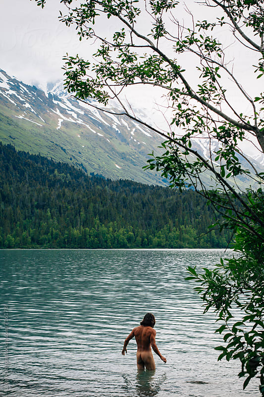 Naked Young Man Wades Into A Mountain Lake by Luke Mattson for Stocksy United