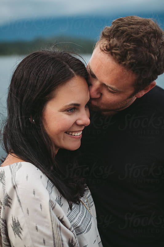 Young man kissing smiling woman on forehead  by Rob and Julia Campbell for Stocksy United