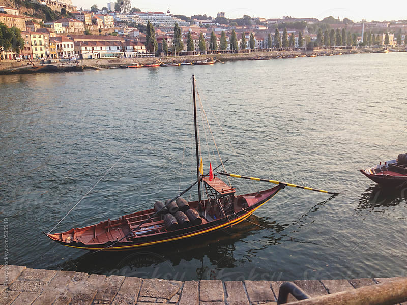 Typical rabelo boat and Porto historical district in background, Portugal by Luca Pierro for Stocksy United