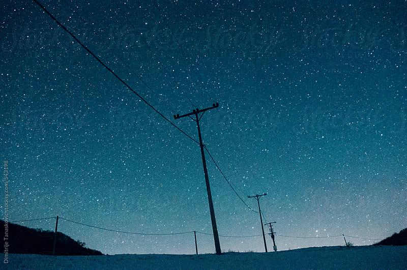 Electric poles under the starry sky by Dimitrije Tanaskovic for Stocksy United