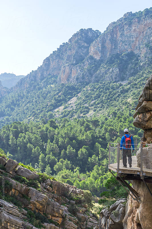 Man walking through a wooden walkway in Caminito del Rey by ACALU Studio for Stocksy United
