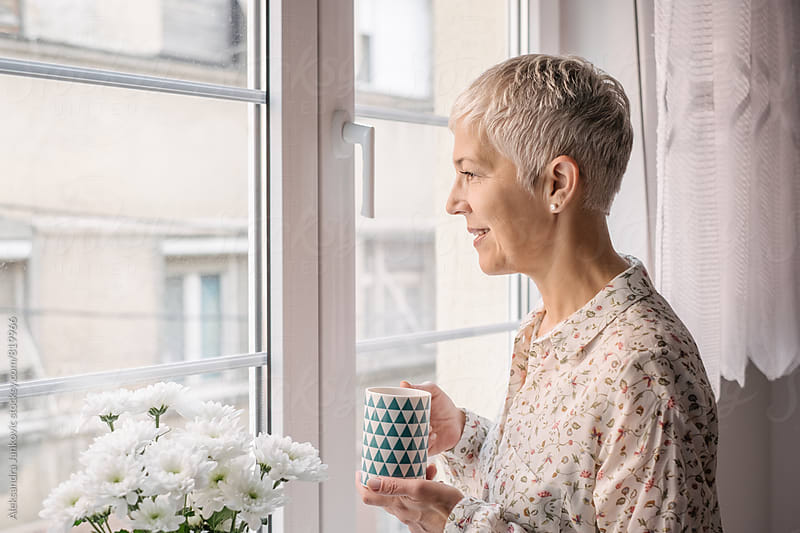 Senior Woman Standing by the Window with Cup of Coffee by Aleksandra Jankovic for Stocksy United